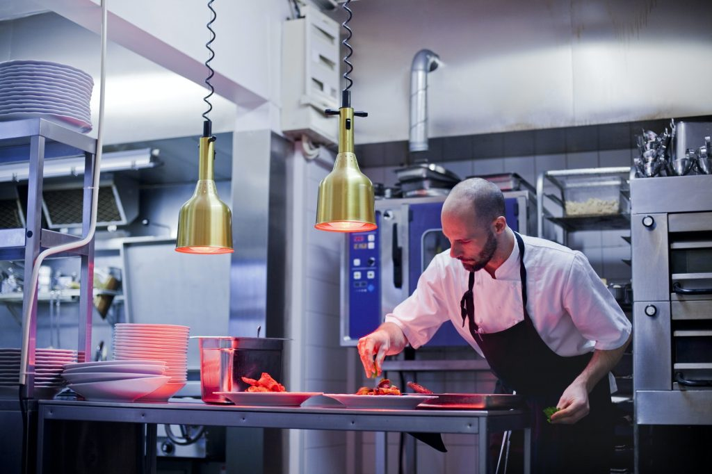 Chef garnishing food at commercial kitchen counter