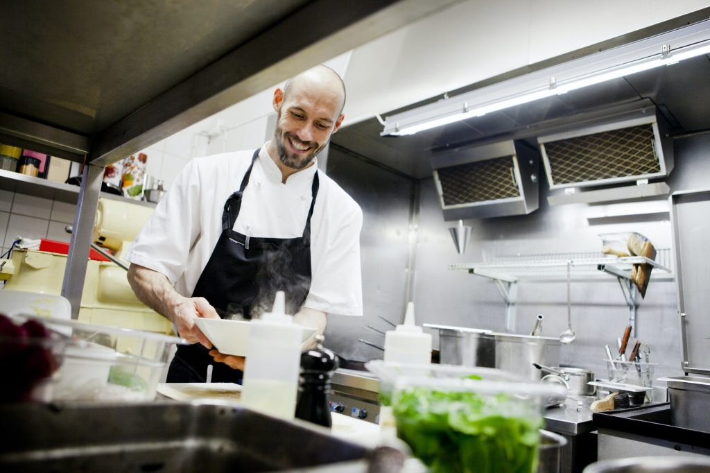 Happy chef holding dish at commercial kitchen