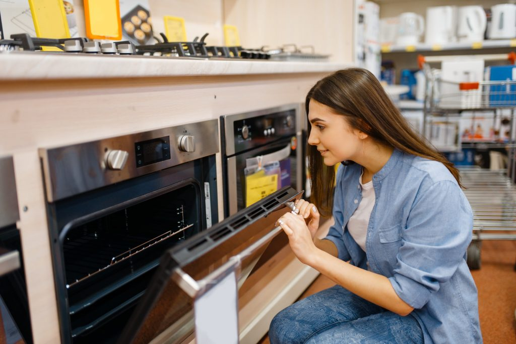 Woman choosing electric oven in electronics store
