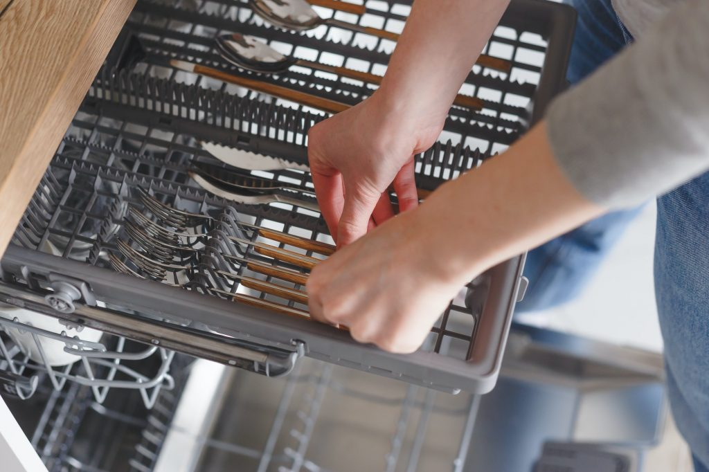 Woman puts cutlery in the dishwasher.